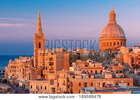 View from above of the domes of churches and roofs at beautiful sunset with churches of Our Lady of Mount Carmel and St. Paul's Anglican Pro-Cathedral, Valletta, Capital city of Malta stock photo