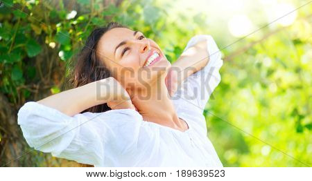 Beautiful Young Woman Enjoying nature Outdoor. Happy and Healthy Smiling brunette Girl with healthy