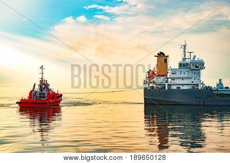 Tanker and tugboat on sea at sunrise.