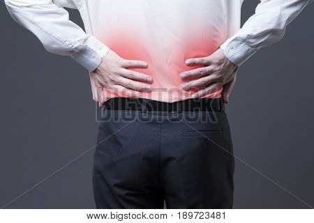 Back pain kidney inflammation ache in man\'s body close-up on gray background with red dot