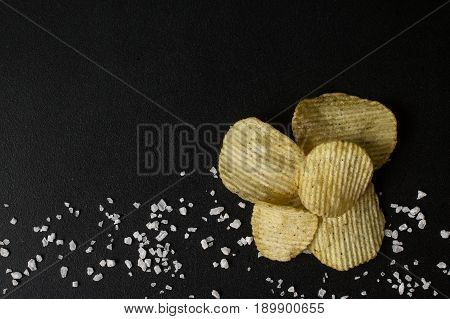 Crinkle cut potato chips on a chalkboard. Tasty spicy potato chips with salt.Top view stock photo
