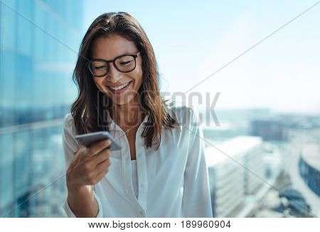 Woman wearing eyeglasses smiling while looking at her mobile phone. Young businesswoman using mobile phone for business communication.