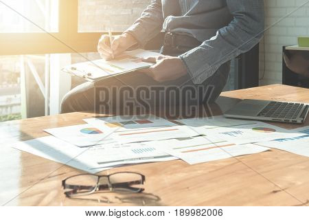 Businessman Analyzing Investment Charts On Document Paper And Using Laptop Computer At Office. Finan