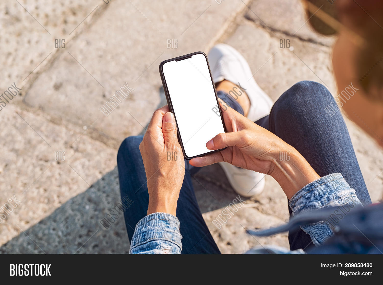 Closeup of young woman hand holding mobile phone with blank screen. Top view of girl using smartphon
