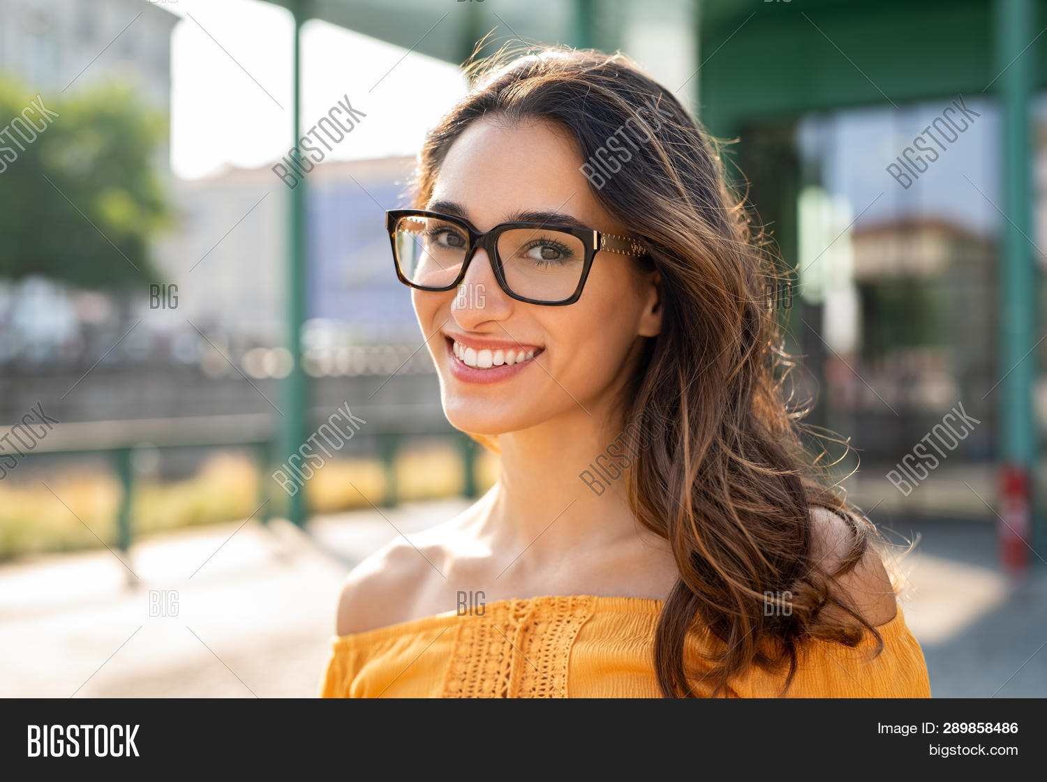 Portrait of carefree young woman smiling and looking at camera with urban background. Cheerful latin
