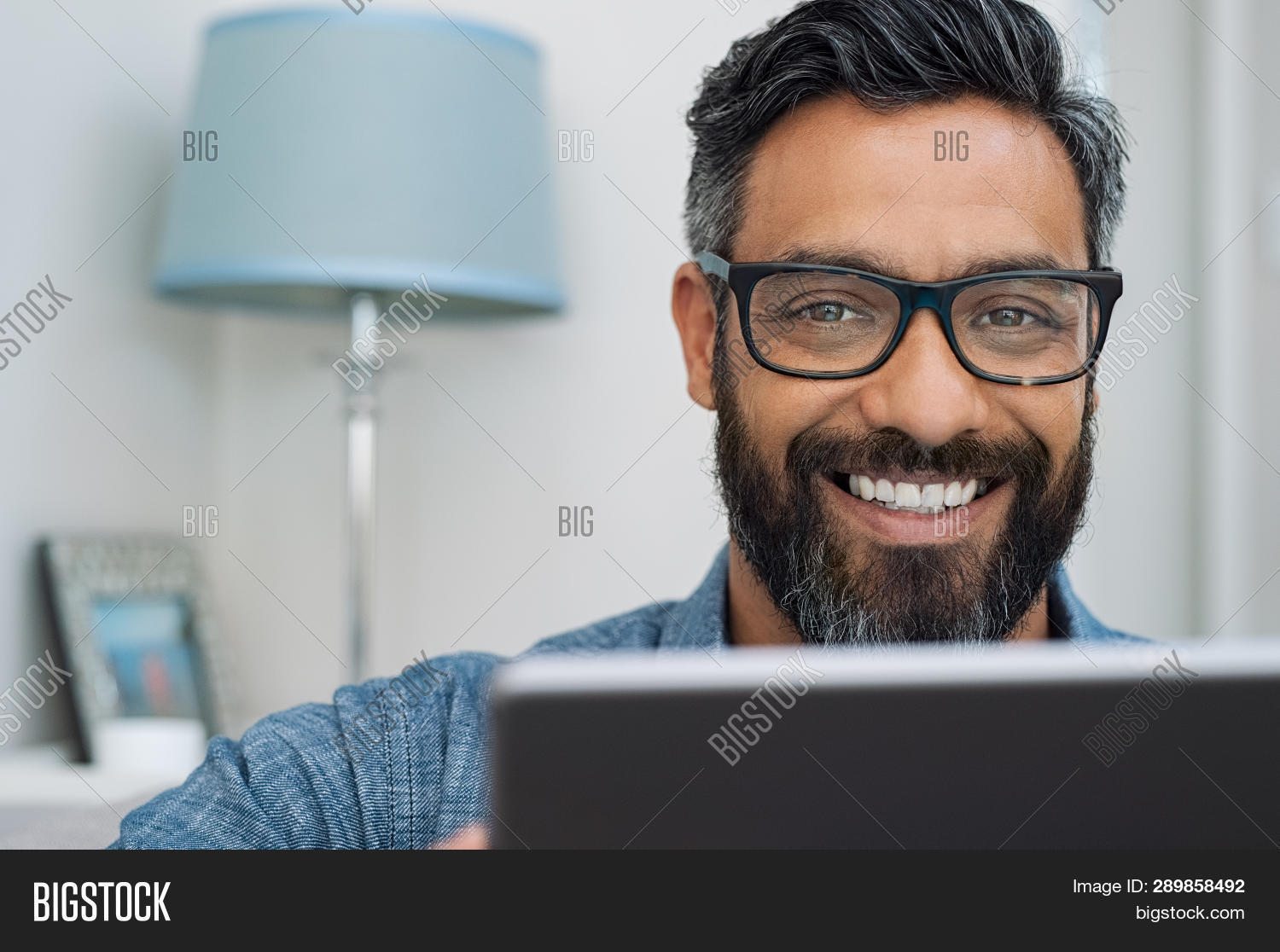 Closeup of businessman wearing glasses and working on laptop while looking at camera. Mature mixed r