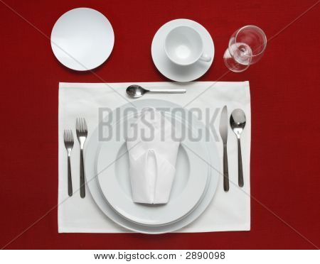 Full table place setting on a red table cloth stock photo