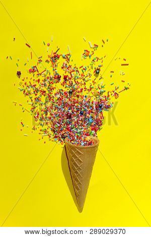 Abstract Colorful Background. Multicolored Candy Sweets On Yellow Background. Closeup Of Multicolored Small Candies. Candy In Ice Cream Cone.Minimal Art Design. stock photo