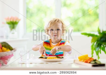 Child eating vegetables sitting in white high chair. Solid food for baby. Little boy eating healthy vegetable lunch of steam cooked carrots. Nutrition for toddler and preschooler. Kids eat fruit. stock photo