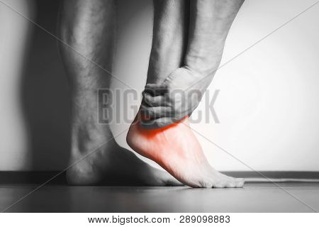 Causian man holds hands to his painful feet, pain in foot.  Black and white photography. red color is area of pain stock photo