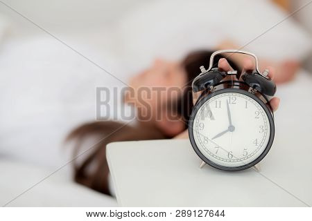 Beautiful asian young woman turn off alarm clock in morning, wake up for sleep with alarm clock, relax and lifestyle concept. stock photo