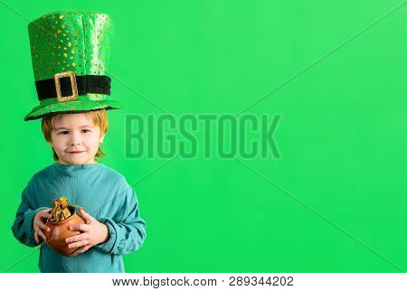 St. Patrick's day celebrations. Traditions of Saint Patrick Day. Cute boy holds pot of gold. Little boy with Leprechaun hat. Coin. Money. Kid in green costume and leprechaun top hat with golden buckle stock photo