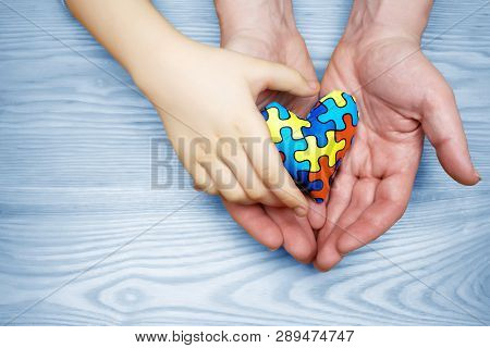 World Autism Awareness day, puzzle or jigsaw pattern on heart with autistic childs and father hands stock photo