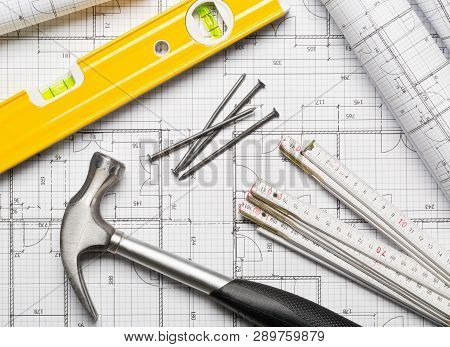 Construction tools  with hammer, nails, folding rule and level on architectural blueprint plan background flat lay top view from above stock photo