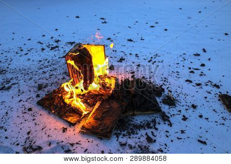 Burning Book In  Snow. Pages With The Text In  Open Book Burn With  Bright Flame.