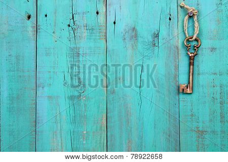 Bronze skeleton key hanging by rope on antique teal blue distressed wood door