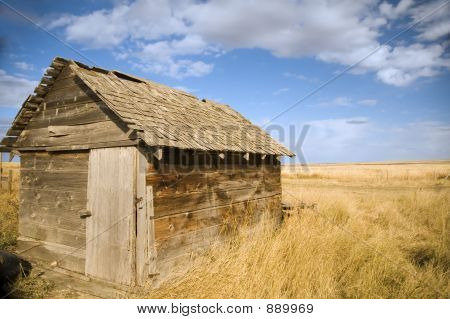old wooden shed on farm under a blue sky. stock photo