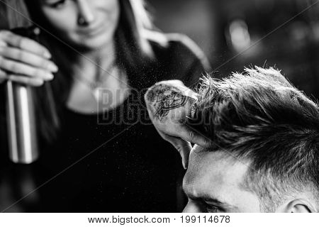Hair styling man in hair salon blak and white image close up man and woman stock photo