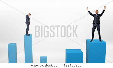 A sad businessman prepares to step down on a low column and a winner beside him who just stepped up on a higher one. Business profits and losses. Entrepreneur's risks. Winner and loser. stock photo