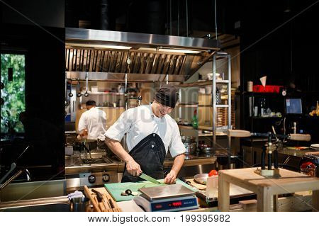 Cook cut vegetables in the kitchen In a restaurant stock photo