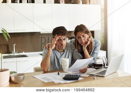 Unhappy American Couple Managing Home Accounts In Kitchen, Trying To Save Some Money By Cutting Fami