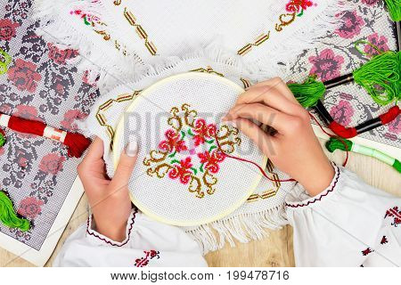 Hands of girl / woman / female in ukrainian traditional shirt sewing embroidery pattern in embroidery frame. Embroidery schemes and colorful threads on background. stock photo