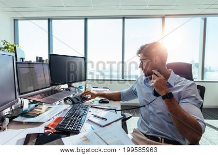 Businessman working in his office with computers and business papers on table. Young entrepreneur making a call using a telephone at his office desk.