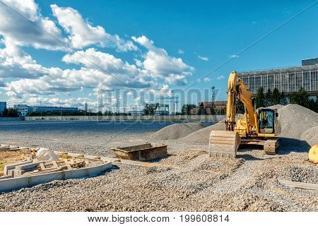 the image Tracked excavator on a construction site among piles of crushed stone stock photo