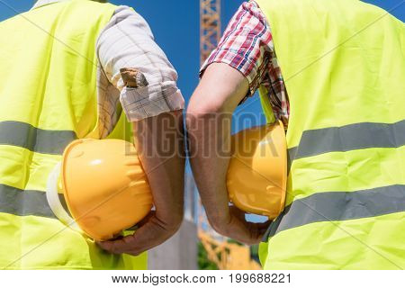 Close-up rear view of the hands of two workers wearing reflective safety vests while holding yellow