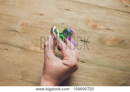 A man hand holding hand spinner or fidget spinner over wooden background. stock photo