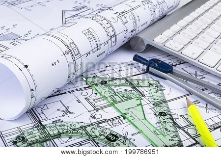 Architectural blueprints drawings of the modern house with computer keyboard. Architectural blueprints and blueprint rolls and a drawing instruments on the worktable. Drawing compass plans. stock photo