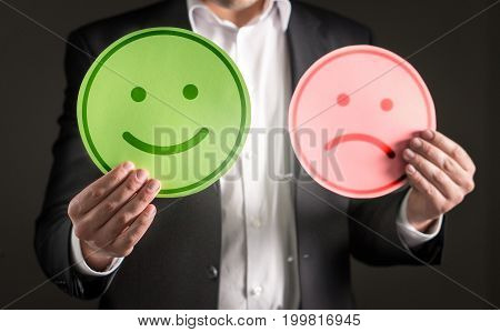 Business man with happy smiling and sad unhappy cardboard paper smiley face emoticon. Rating and giving review about customer satisfaction or team spirit in company.