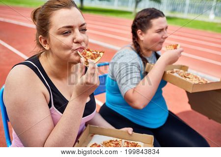 Hungry over-sized females eating pizza after workout on stadium stock photo