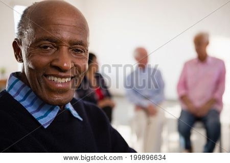 Close up Portrait of smiling senior man with friends in background at art class stock photo