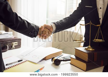 Handshake between attorneys and clients after agreeing to enter into a contract for a court case. In the hope of victory over legal fighters. stock photo