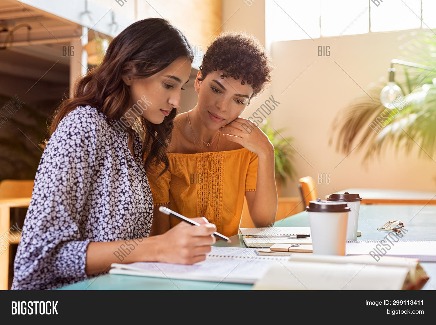 Young multiethnic women studying together at library. High school or college students studying and r