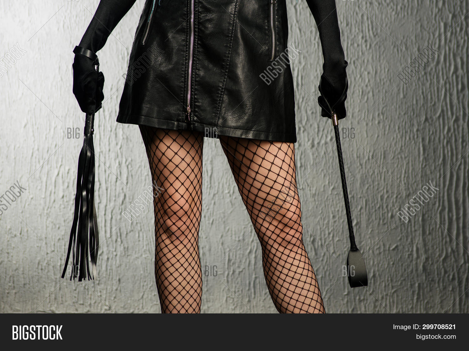 The Dominant Woman In A Leather Dress With A Stack And A Whip In Her Hand. Bdsm Outfit - Image