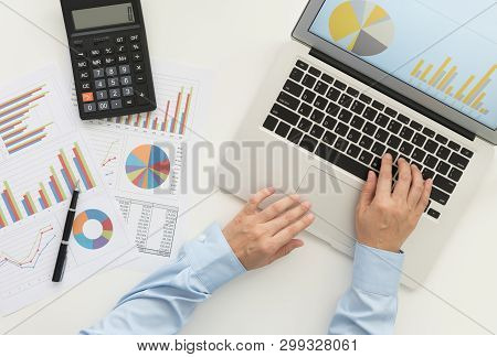 Financial analyst using laptop computer analyzing business data on desk. top view. Accounting concept. stock photo