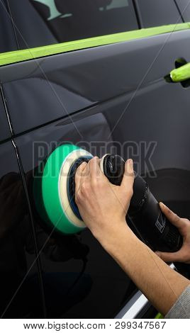 Car polish wax worker hands polishing car. Buffing and polishing vehicle with ceramic. Car detailing. Man holds a polisher in the hand and polishes the car. Tools for polishing stock photo