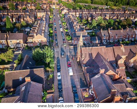 Sun setting with atmospheric effect over traditional British houses and tree lined streets. Dramatic, warm lighting creates a homely mood. Very typically English houses that are over 100 years old. A picturesque scene, created by the long shadows and warm stock photo