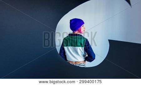 Young girl in 90s style jacket and twisting black paper on white background stock photo