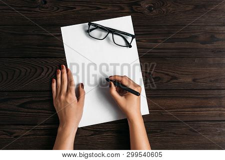 Top view of women's hands, ready to write something on an empty piece of paper lying on a wooden table. Write a letter on a white sheet. Hands, blank sheet, pen and glasses on wooden table stock photo