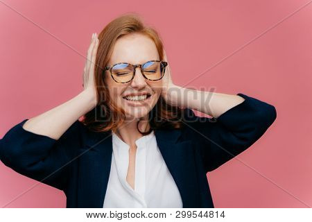 Frustrated young businesswoman has headache, ignores loud noise, covers ears with hands, clenches teeth, has closed eyes, wears elegant black and white formalwear, isolated on pink background stock photo