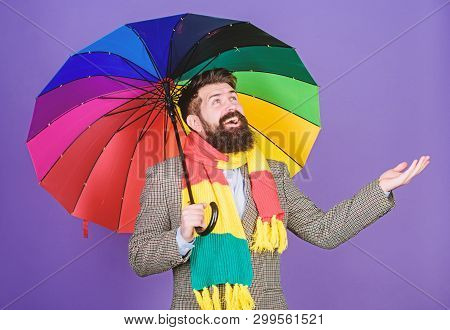 An umbrella is needed on a rainy day. Autistic or rain man holding colorful umbrella. Autism. Bearded man checking if it rains. Fashion man with colorful accessories. Let it rain stock photo