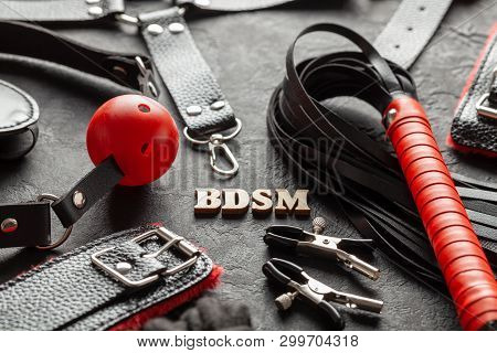 BDSM sex toys for adults. On black background whip, gag, handcuffs and leather straps. stock photo