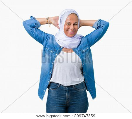 Middle age eastern arab woman wearing arabian hijab over isolated background Relaxing and stretching with arms and hands behind head and neck, smiling happy stock photo
