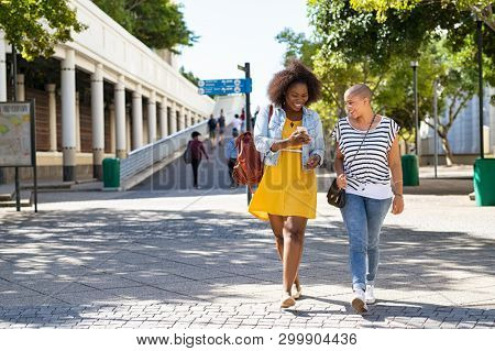 Two young women walking while using mobile phone on urban city street. Cheerful woman doing online shopping with friend outdoor. African american girl showing smartphone screen to friend. stock photo