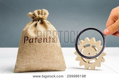 Money bag with the word Patents and a wooden gear. Registration of patents and copyright compliance. Licensing technology and scientific discoveries. Purchase and sale of patents. Royalties stock photo