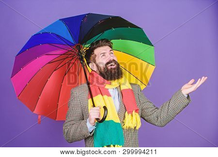 Looking like its going to rain. Autism. Autistic rain man holding colorful umbrella. Bearded man checking if it rains. Fashion man with colorful accessories. He never needs to worry about rainy days stock photo