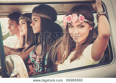 Multi-ethnic hippie friends in a minivan on a road trip